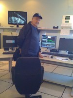 Dr. Massimo Tarenghi stands in the middle of the cerebral cortex of the 8.2 meter telescope (seen on the monitor above his right shoulder) as data on weather is presented on the screen in the middle.