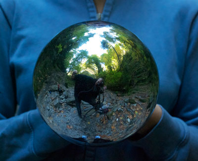 Cheryl Hebert holds mirror ball on location in BC's coastal rainforest