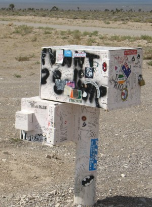 "The ""black mailbox"" is actually dirty white and covered with graffiti"