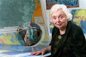 Marie Tharp in her later years with her famous maps and globes behind her.